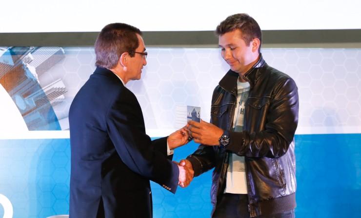 Anderson dos Santos, segundo colocado, sendo premiado pelo Reitor da FAE, Frei Nelson José Hillesheim.